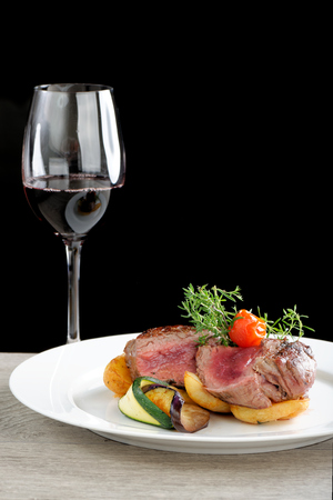 A dinner setting: Juicy grilled bbq steaks with fresh herbs, potato, vegetable and a glass of a good red wine photo
