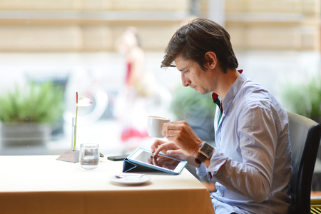 Young fashion man  hipster drinking espresso coffee in the city cafe during lunch time photo