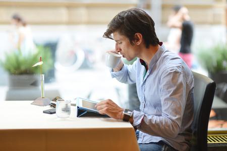 cafe internet: Joven hombre de moda  pantalones de tiro bajo consumo de caf� espresso en el caf� de la ciudad durante la hora del almuerzo y de trabajo en equipo Tablet PC