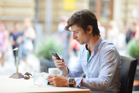 Young fashion man  hipster drinking espresso coffee in the city cafe during lunch time and working on tablet computer photo