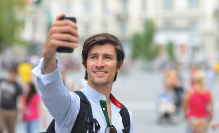 generation y: Student  tourist taking self portrait in the europe street Stock Photo