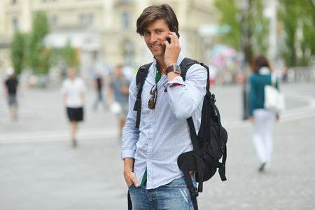 Student with the mobile smart phone walking, background is\ blurred city