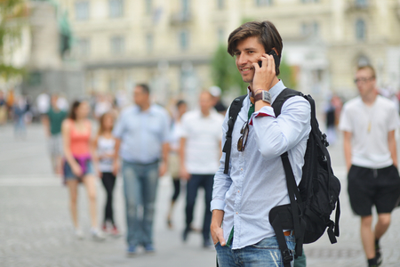 Student with the mobile smart phone walking, background is blurred city photo