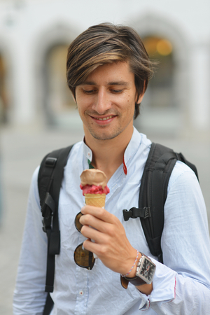 25 30 years: Portrait of handsome young man eating ice cream on the street