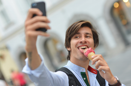 Selfie of handsome young man eating ice cream on the street photo