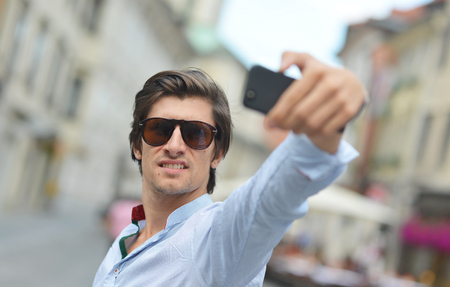 Young fashionable hipster Hispanic man with sunglasses taking a selfie on the city street photo