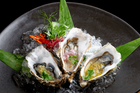 Fresh Oysters with three sauces (cilantro with lime juice, ginger vanilla and pinneaple with chili) Stock Photo