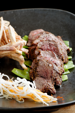 Lemongrass grilled beef steak with snow peas and taro potatoes photo