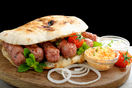 Cevapcici, a small skinless sausage cooked on the barbecue and served with: Lepinja bread, pickled red capsicum and Kajmak cheese. This dish is popular all over the Balkans, with tourists and locals. photo