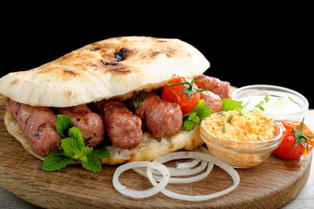 Cevapcici, ein kleines hautlosen Würstchen auf dem Grill zubereitet und serviert: lepinja Brot, eingelegte rote Paprika und Kajmak Käse. Dieses Gericht ist beliebt in der ganzen Balkan, bei Touristen und Einheimischen. Standard-Bild - 33349894