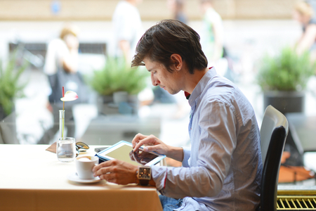 Young fashion man  hipster drinking espresso coffee in the city cafe during lunch time and working on tablet computer Imagens