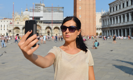 take a history: A beautiful young woman taking herself a selfie in Venice, Italy on Piazza San Marco