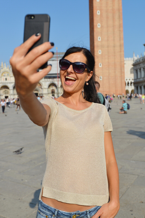 narcissist: A beautiful young woman taking herself a selfie in Venice, Italy on Piazza San Marco