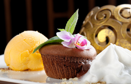 Fine dining, Chocolate souffle with mango ice cream and coconut foam photo