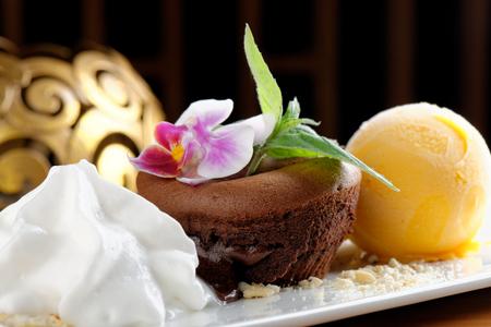 Chocolate souffle with mango ice cream and coconut foam photo