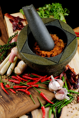 Asian herbs, spices and vegetables on the wooden plate with mortar making curry paste