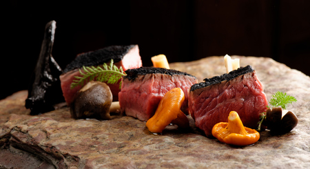 Delicious medium beef steaks with mushrooms on the wood photo