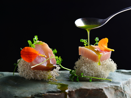 cuisine: Fine dining, fresh raw ahi tuna sashimi served on sponge with herbs Stock Photo