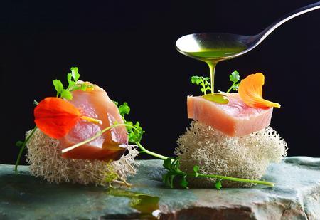Fine dining, fresh raw ahi tuna sashimi served on sponge with herbs photo
