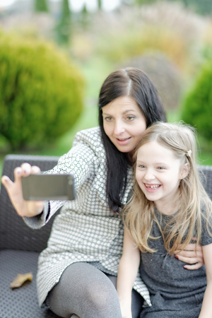 Mother and daughter sitting in nature and talking selfie with a smartphone photo
