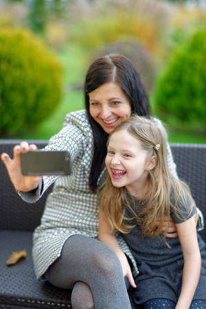 Mother and daughter sitting in nature and talking selfie with a smartphone Imagens