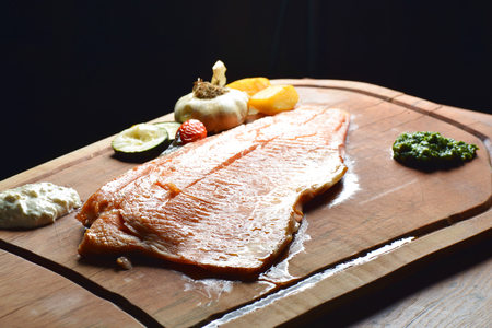 Smoked wild salmon fillet with vegetable on wooden board photo