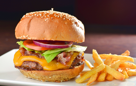 burgers: Cheese burger with a bacon - American cheese burger with fresh salad and french fries Stock Photo