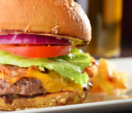 Cheese burger with a bacon - American cheese burger with fresh salad and french fries photo