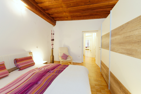 Stylish white bedroom with a purple bed photo