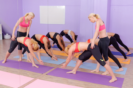 Bikram Hot Yoga Class instructor with students Stock Photo