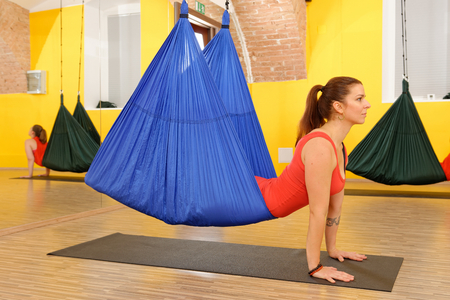 Frauen, die Antischwerkraft Aerial Yoga-Übung in der Turnhalle