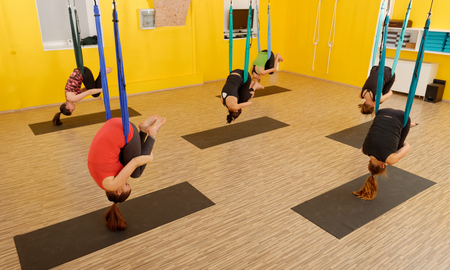 Women doing anti gravity Aerial yoga exercise in the gym photo