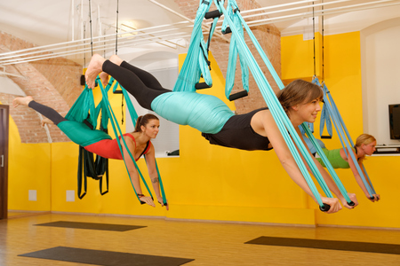 the trapeze: Women doing anti gravity Aerial yoga exercise in the gym