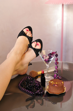 Sexy legs with high heel shoes, jewelry, pearls, lipstick and a chocolate cake photo