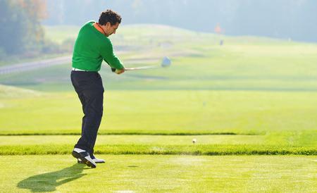 Golfer swing, teeing off on beautiful summer morning photo