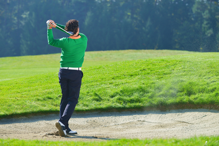 Golfer chipping the ball from sand trap, golf ball in the air. photo