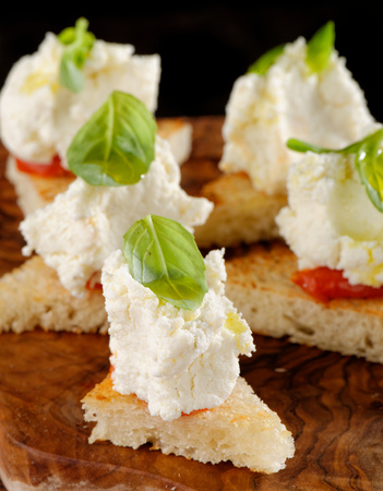 Spanish food tapas. Toasted bread with fresh cheese and vegetables photo