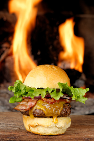 bacon night: Gourmet bacon cheeseburger with lettuce and tomato in front of the fire Stock Photo