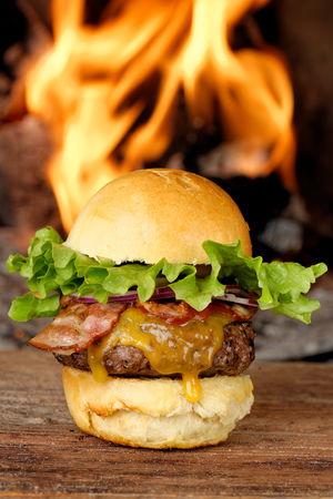 Gourmet bacon cheeseburger with lettuce and tomato in front of the fire photo