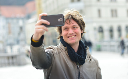 generation y: Young handsome hipster man making funny selfie in the city Stock Photo