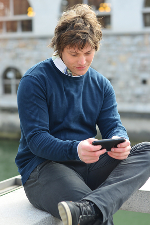 message sending: Portrait of young guy sending message with smartphone Stock Photo