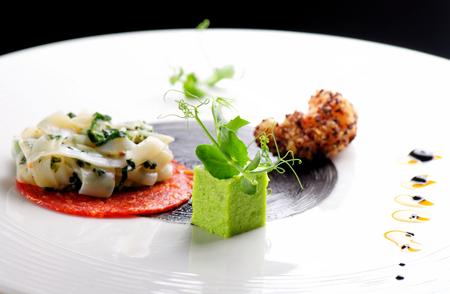 Haute cuisine, Gourmet voorgerecht, inktvis, garnalen tempura en Chorizo Stockfoto