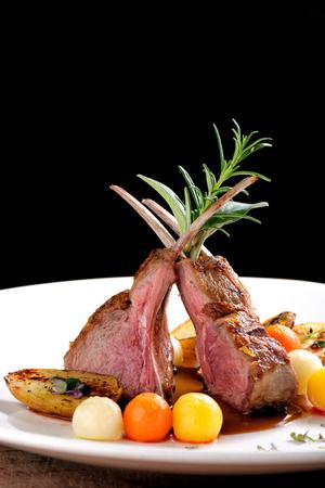 Lekker eten, geroosterde lamskoteletten met aardappel, rozemarijn en plantaardige saus