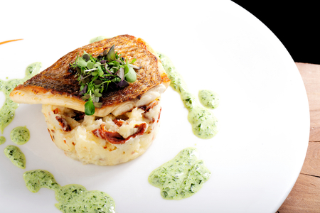 perch dried: Tasty healthy fish fillet with potato puree with dried tomatoes and wild garlic sauce Stock Photo