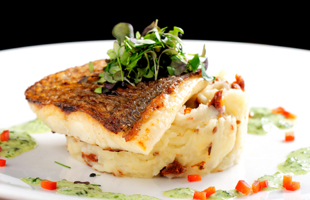 Tasty healthy fish fillet with potato puree with dried tomatoes and wild garlic sauce Imagens