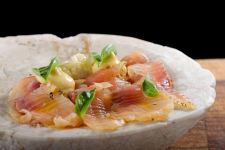forefront: Fresh Tuna carpaccio with basil, radish, onion and olive oil