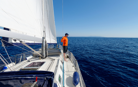 sailing: Man sailing with sails out on a sunny day