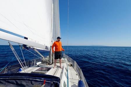 sailing crew: Man sailing with sails out on a sunny day