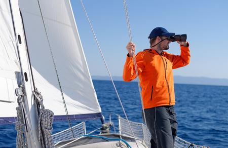 bateau voile: Man voile avec des voiles dehors sur une journée ensoleillée Banque d'images