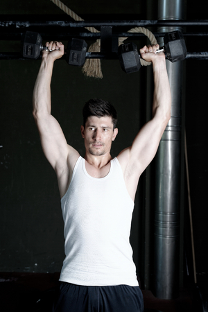 musculation: very power athletic guy , execute exercise with dumbbells, on bkack background